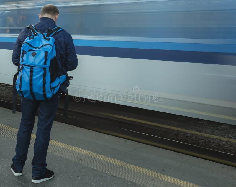 En man som väntar på drevplattformen och ett ankommande blått drev av Cesken Drahy på Prague den huvudsakliga drevstationen arkivfoton