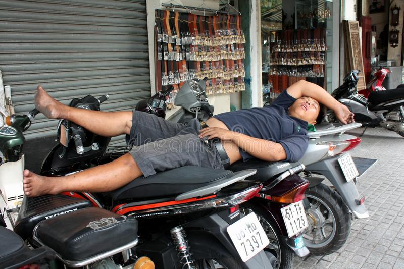 En man sover på motorcyklar Vietnam Ho Chi Minh City fotografering för bildbyråer