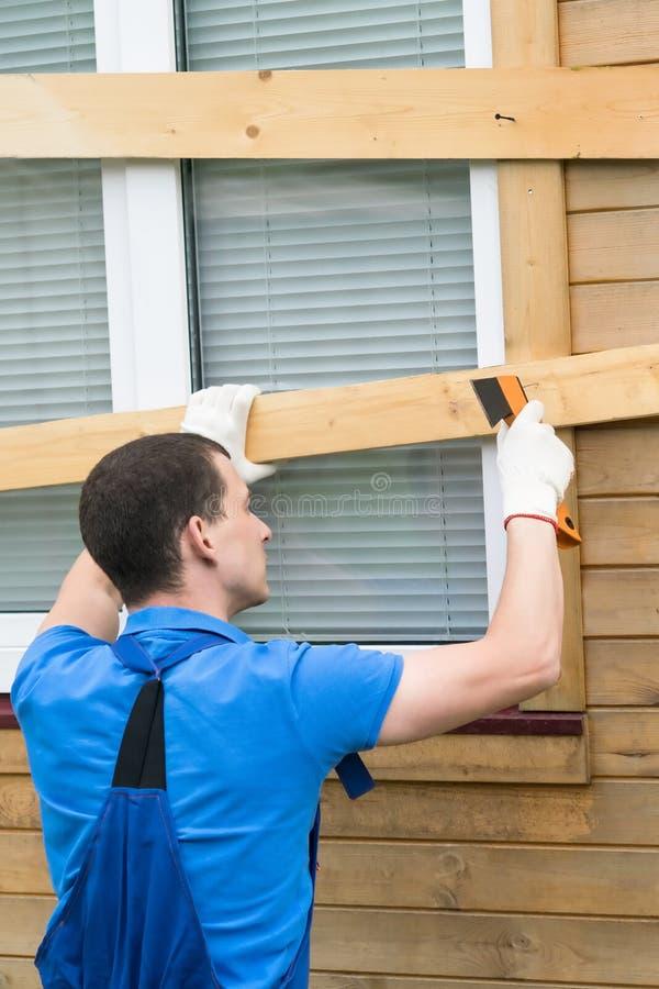 En man sparkar spikar in i plankor på ett fönster, stänger dem från naturkatastrofer arkivfoton