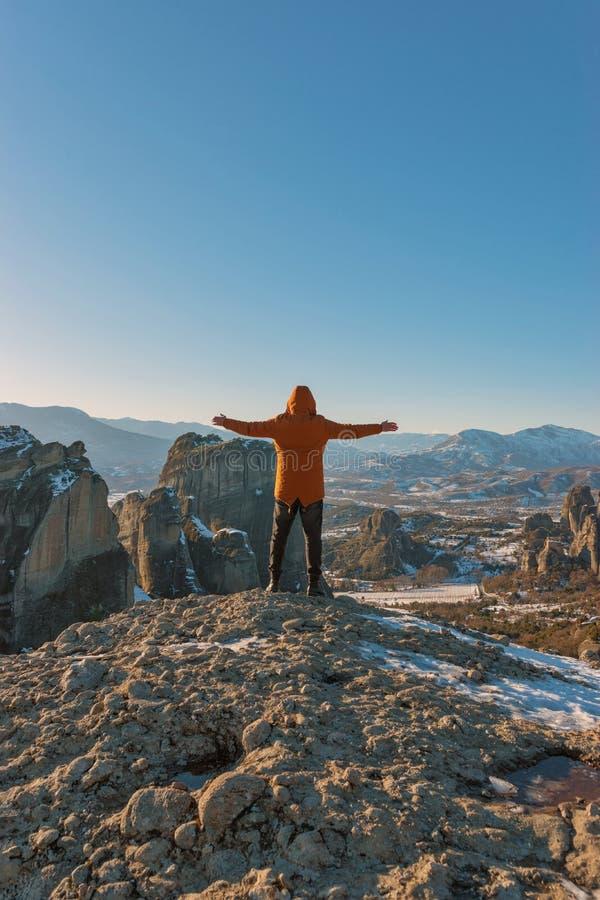 En man står överst av steniga berg och tycker om den härliga sikten av den Meteora kloster i Grekland royaltyfri bild