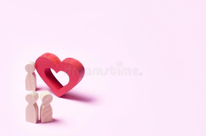 En man står nära hjärtan och bekänner förälskelse på en rosa backgro arkivbilder