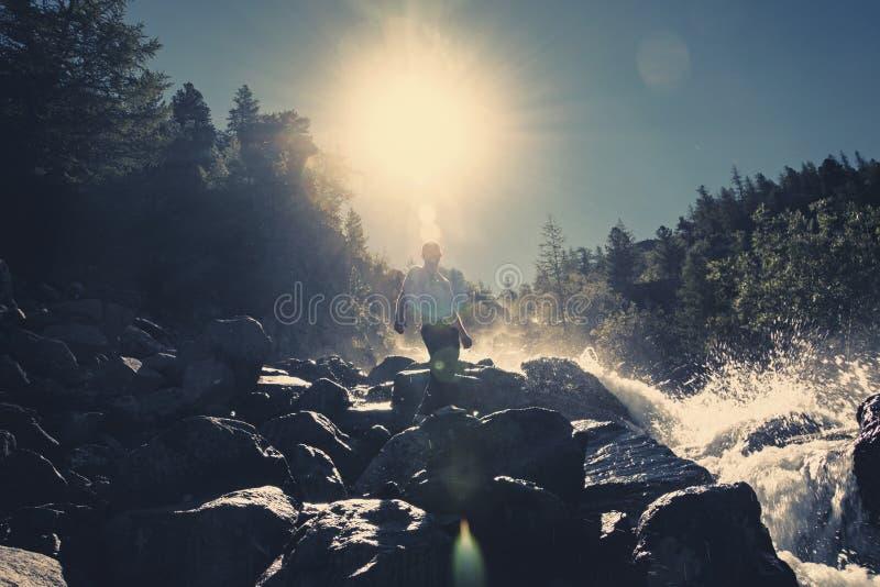 En man står på en sten mot en vattenfall under den ljusa solen vattenfall i skogen en sprej av vatten royaltyfri bild