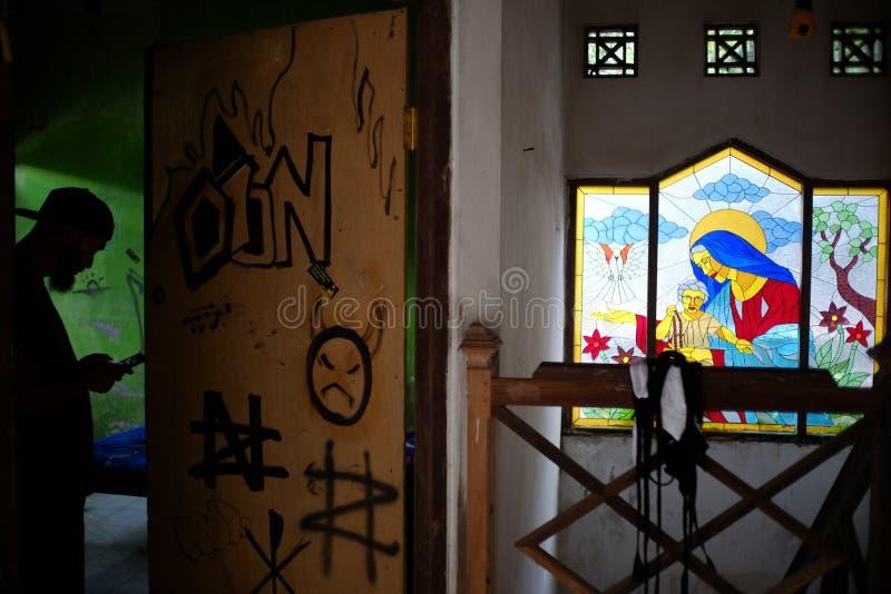 En man står vid dörren med vandalism av demonsymbolet och religiösa prydnader i det dekorativa exponeringsglaset av huset royaltyfria bilder