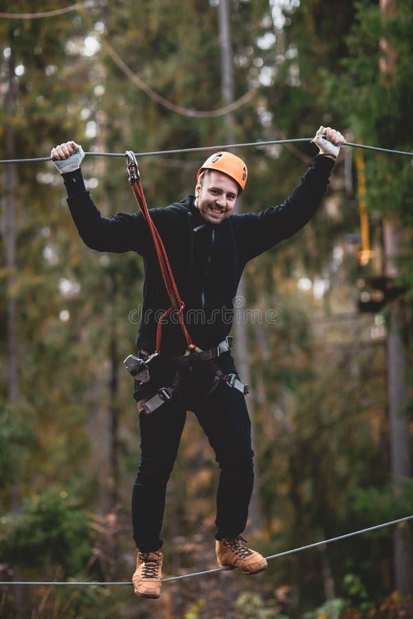 En man stiger ned på ett rep, en sport i en ytterlighet parkerar, arkivfoto