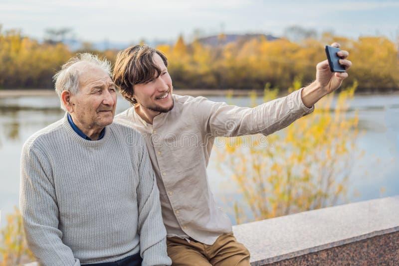En man tar en selfie med en äldre man royaltyfri bild