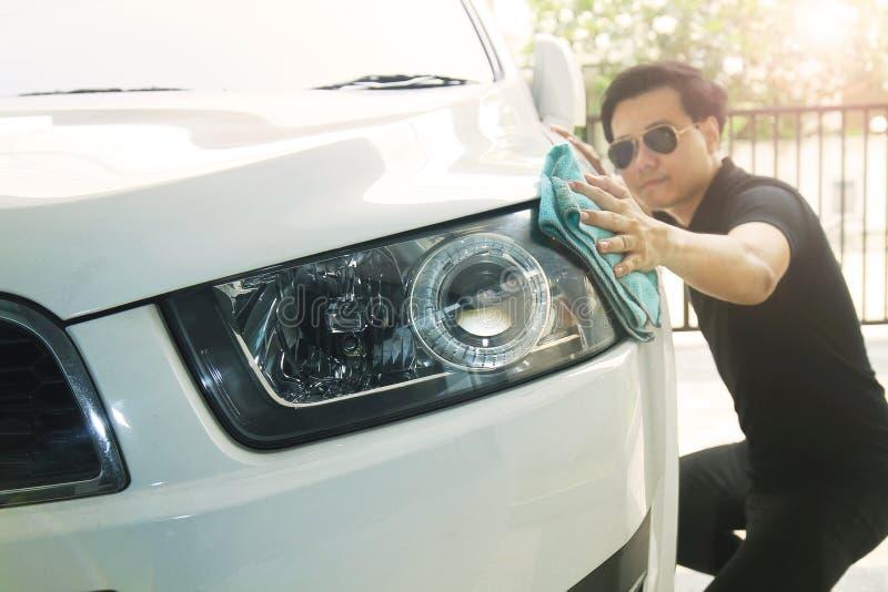 En man torkar bilen med en microfibertorkduk Håll detaljer som fokuserar på billyktorna royaltyfri foto