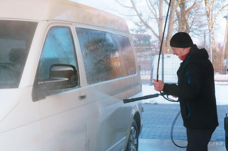 En man tvättar en skåpbil på en biltvätt i vintern, washes för en man en vit skåpbil arkivbild
