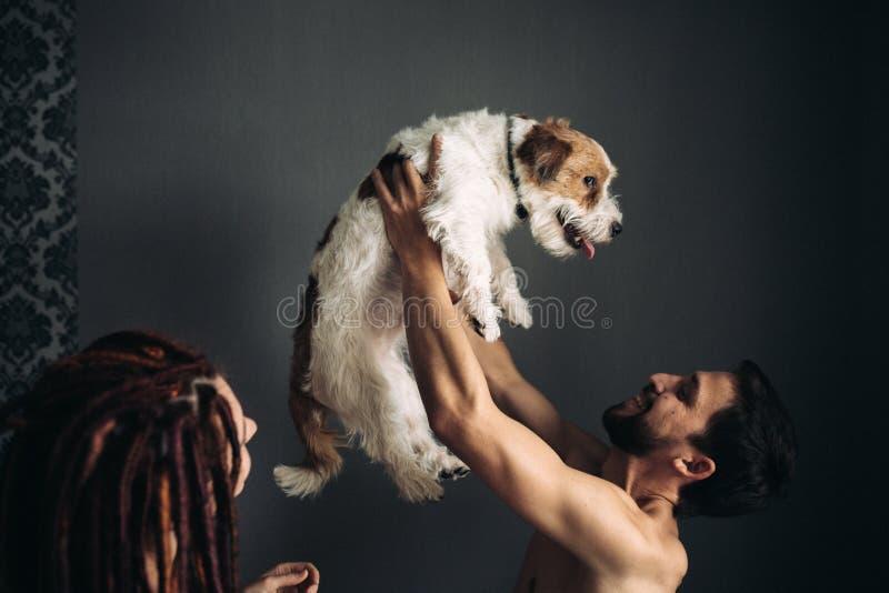 En man utan en skjorta rymmer en hund p? hans utstr?ckta armar royaltyfri foto