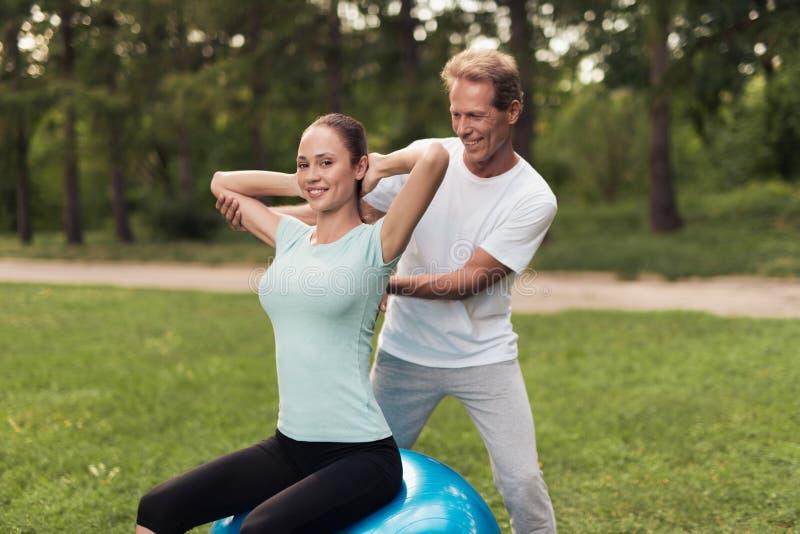 En man utbildar en kvinna som gör övningar, medan sitta på en boll för yoga i parkera fotografering för bildbyråer