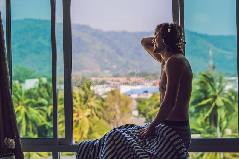 En man vaknade upp i morgonen och lyssnar till musik i trådlös hörlurar på bakgrunden av förbise för fönster arkivfoto