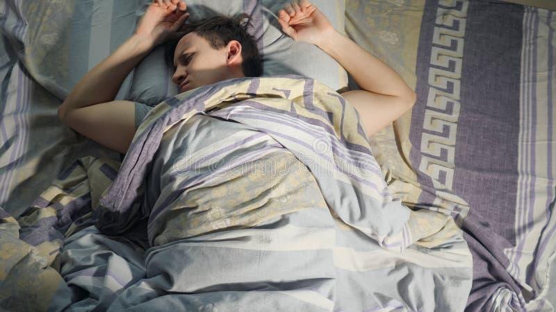 En man vaknar från mardröm, dålig dröm och rastlös sömn på natten arkivfoto