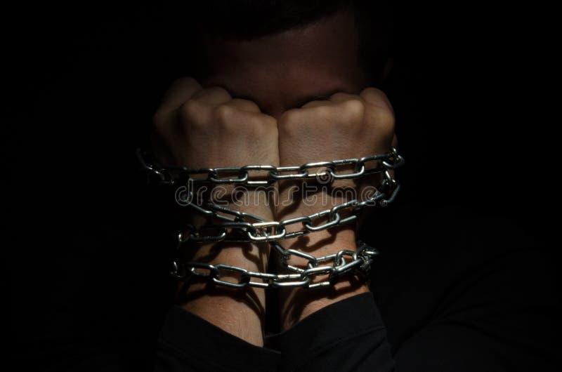 En manfånge som kedjas fast i en kedja som klamra sig fast intill hans huvud mot en svart bakgrund royaltyfri bild