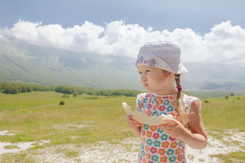 En mangeant le melon doux découpez la petite fille en tranches appréciant la vue alpine images stock