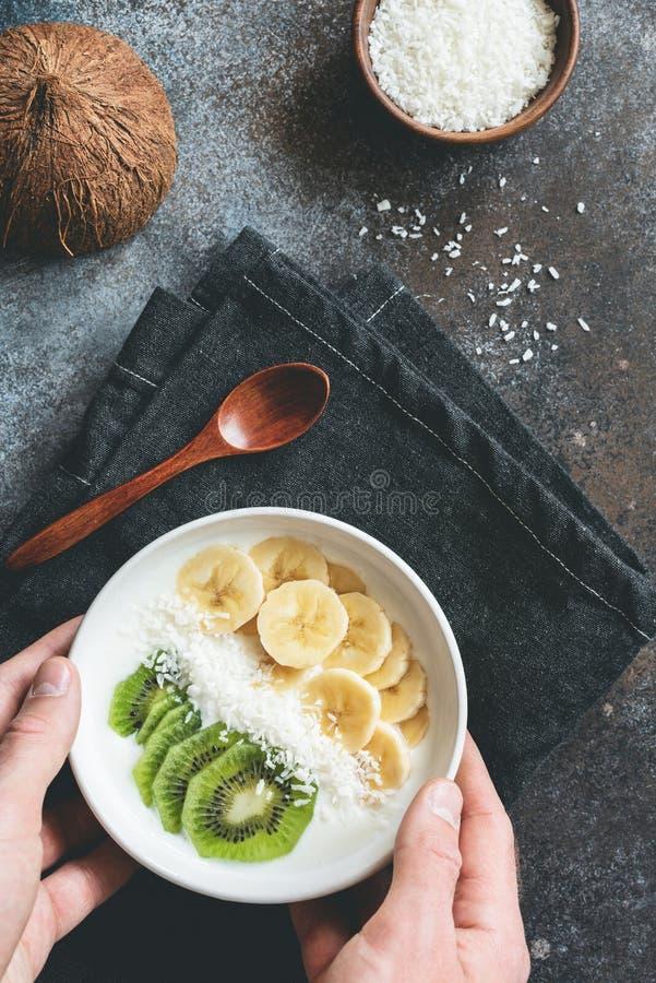 En mangeant le smoothie roulez pour des mains de petit déjeuner tenant le bol de smoothie de vegan avec du yaourt, le kiwi et la  photo stock