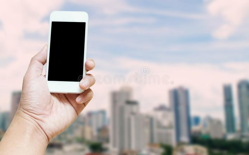 En manhand som rymmer den tomma skärmen av suddig fotourb för smart telefon arkivbilder
