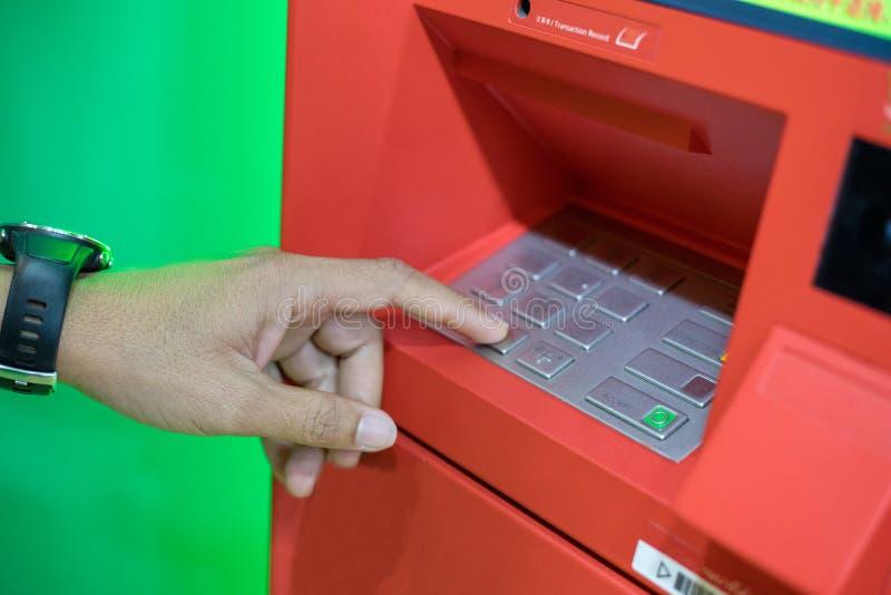 En manhand som skriver in PIN-/passkod på ATM-/bankmaskintangentbord arkivbilder