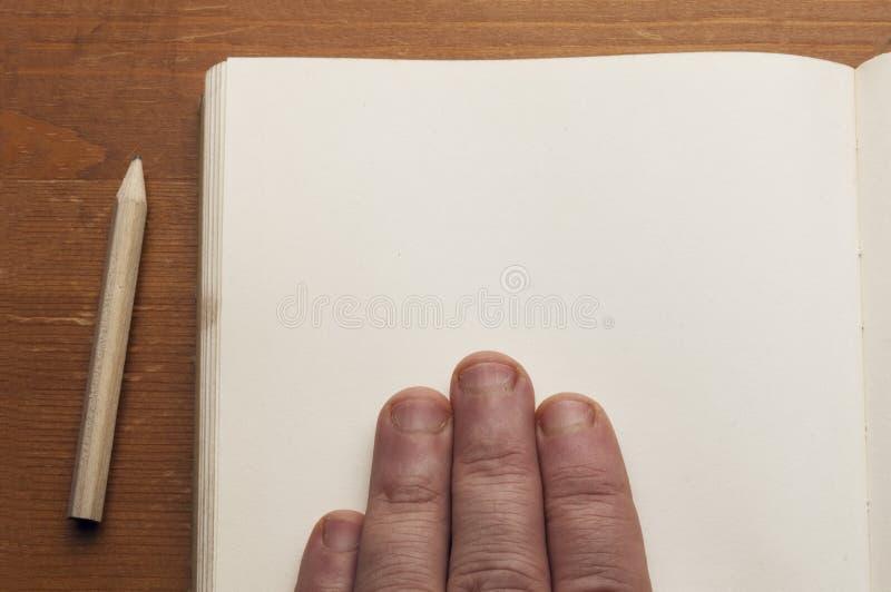 En maninnehavhand på den gamla boken med den tomma sidan på trätabellen med en liten blyertspenna arkivbilder
