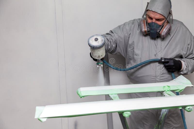 En manlig arbetare målar med en sprutpistol en del av bilkroppen i silver, når han har skadats på en olycka Plast- beståndsdelar  royaltyfria bilder
