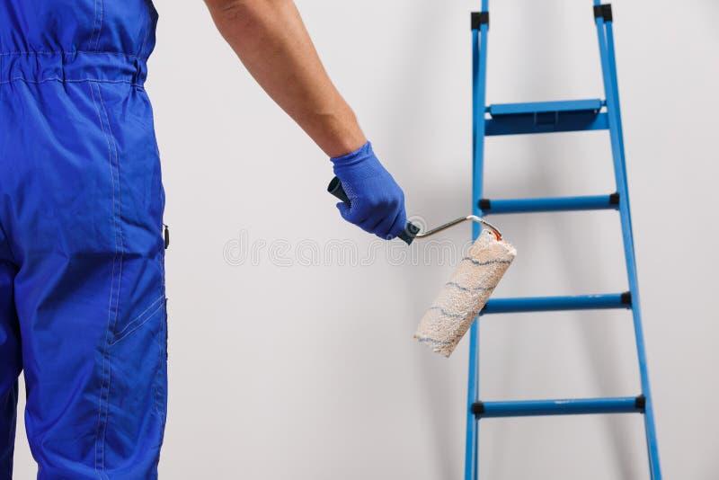 En manlig arbetarmålare, i en blå likformig och handskar som rymmer en skrivmaskinsvals Stående mitt emot väggen med en trappsteg arkivbilder