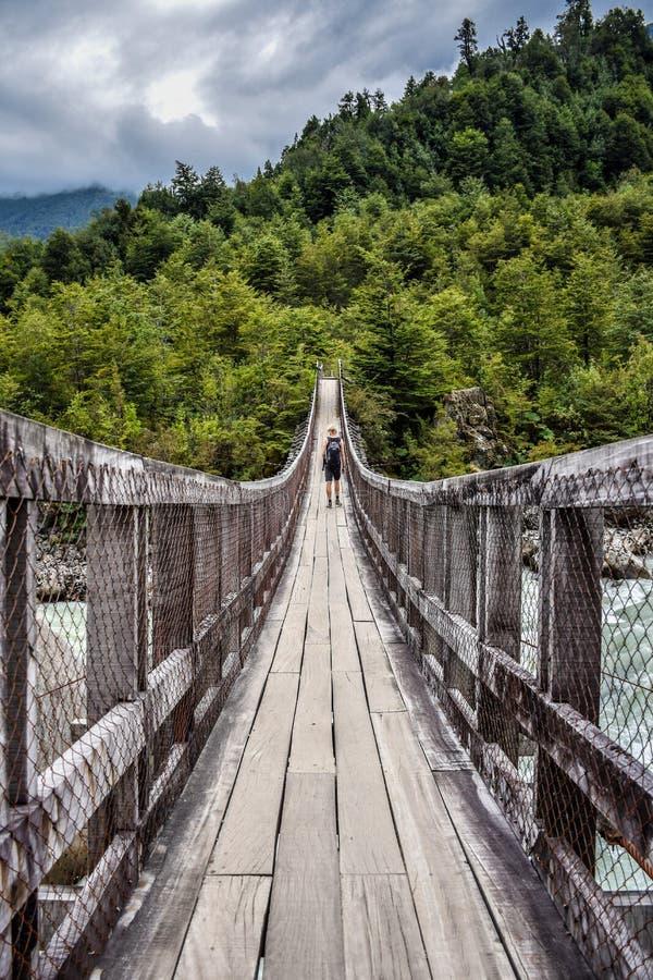En manlig fotvandrare på en träbro över en flod i Chile arkivfoton