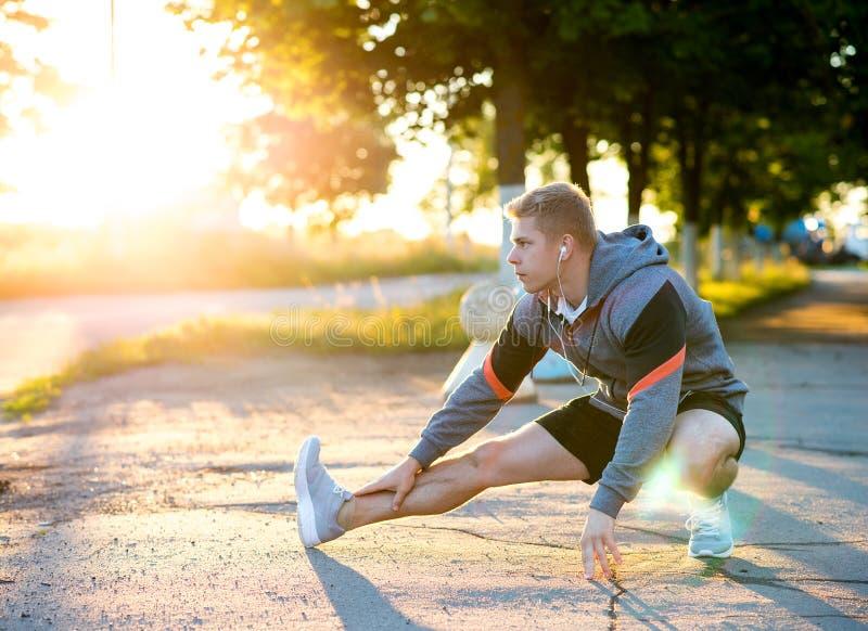 En manlig lagledare knådar hans ben, innan den utbildar med hörlurar Löpare i morgonen i parkera lyssnar musik till royaltyfri foto