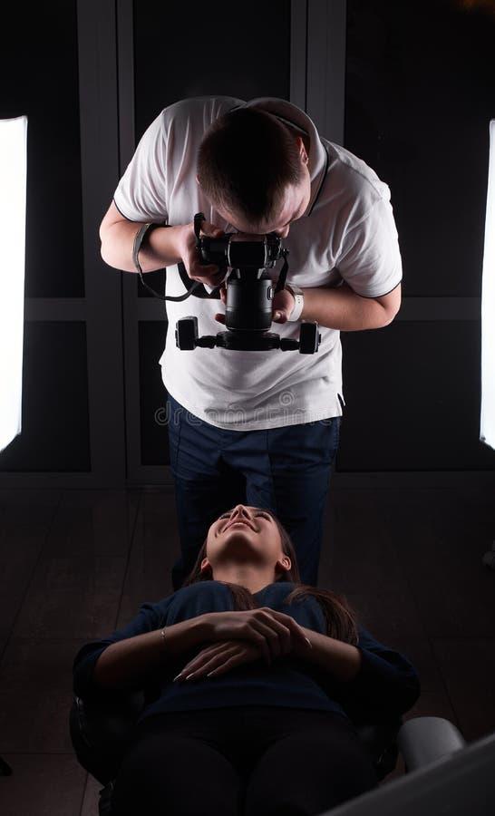 En manlig tandläkare gör en bild av hans kvinnliga klient` s att le att ligga på en lagledare och att le till honom royaltyfria foton