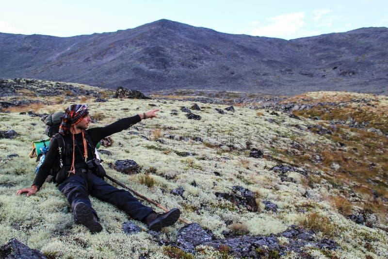 En manlig turist är trött och sitter på en mossa i bergen i en vandring med ett finger visar riktningen royaltyfri bild