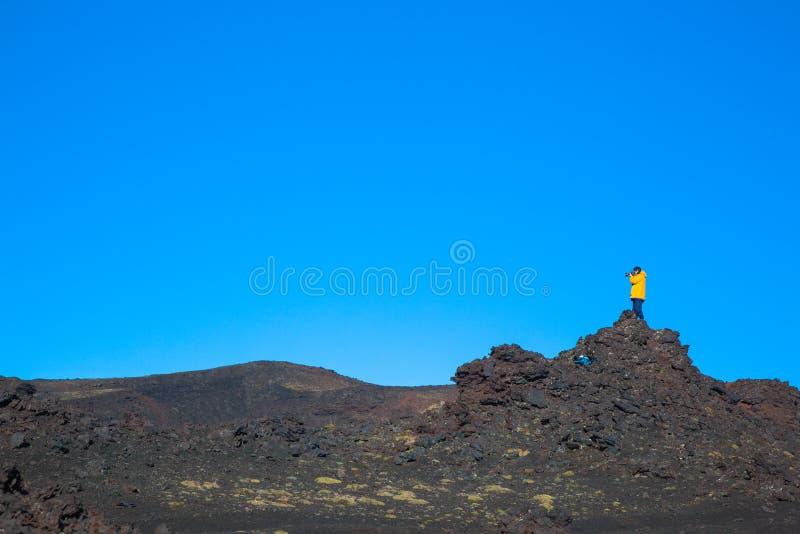 En manphotographe på ett maximalt berg mot en blå himmel arkivbilder