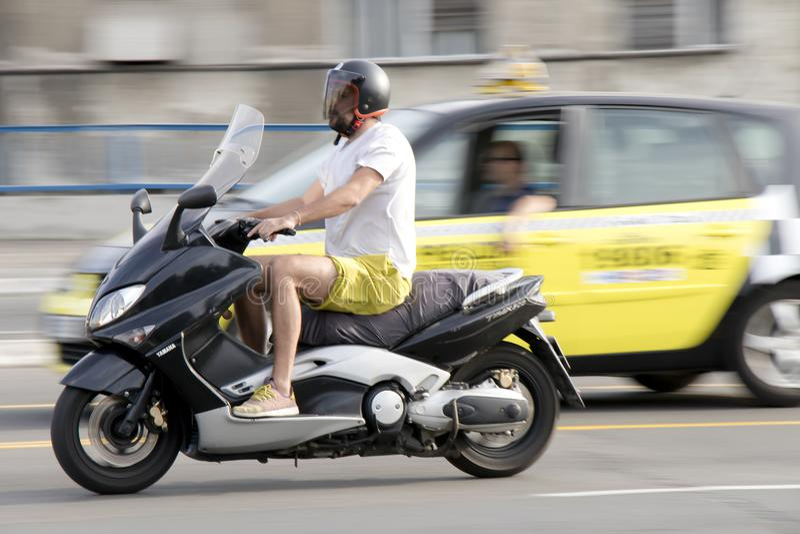 En manridningsparkcykel i stadsgatatrafik royaltyfri bild