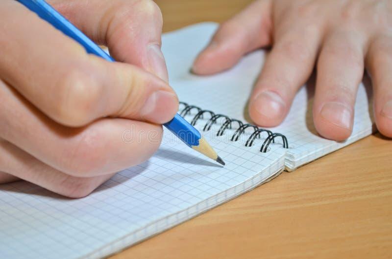 En mans hand i en vit skjorta skriver texten med en blå pensil i en anteckningsbok med en spiral på en trätabell arkivbilder