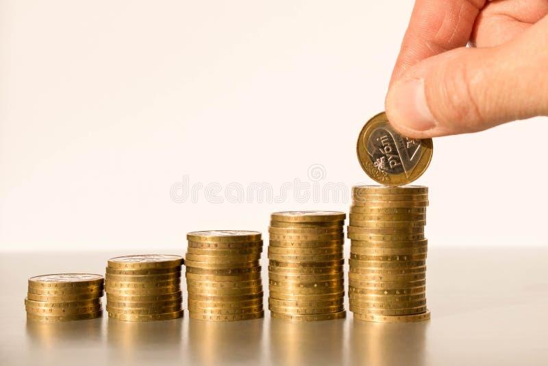 En mans hand som s?tter mynt i buntar Aff?rsid?- och huvudstadtillv?xt royaltyfri bild