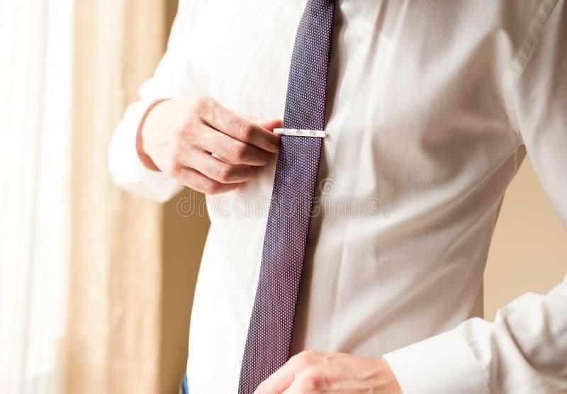En manskjorta justerar hans band royaltyfri foto