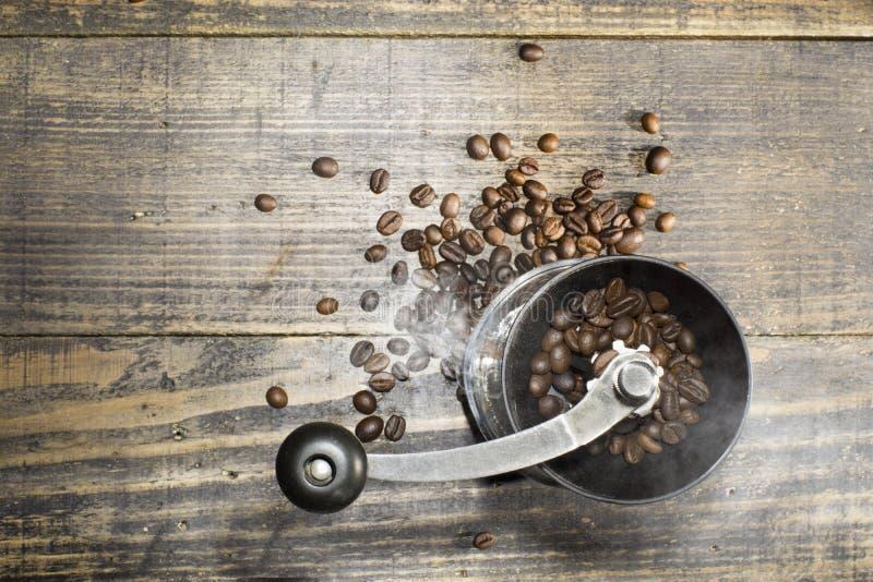 En manuell molar för kaffeböna som innehåller kaffebönor som beskådas från ovanför, är med rök- och kaffebönor på ett träbräde arkivfoto
