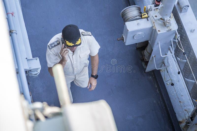 En marin- tjänsteman i likformig och en hatt som promenerar däcket av en krigsskepp michigan för amerikansk auto konvertibel detr royaltyfri bild