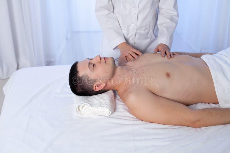 En massageterapeut gör behandlingar för massage och för kropp för manläkarundersökning tillbaka på Spa royaltyfri fotografi