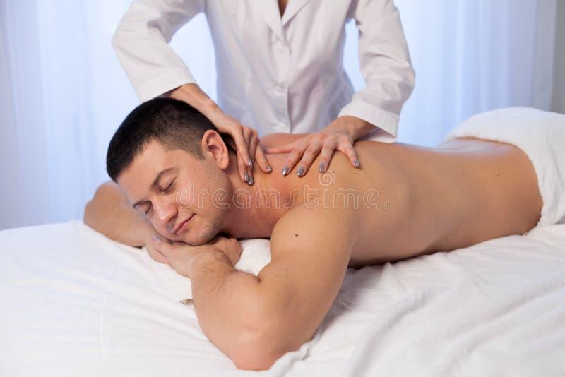 En massageterapeut gör en man att massera brunnsortbehandlinghälsa arkivfoton
