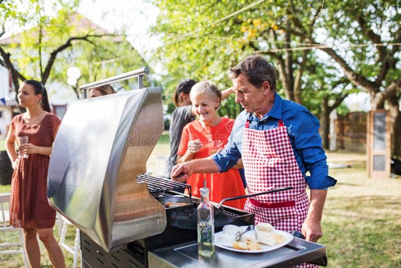 En matlagningmat för hög man på gallret på ett grillfestparti utanför i trädgården royaltyfria bilder