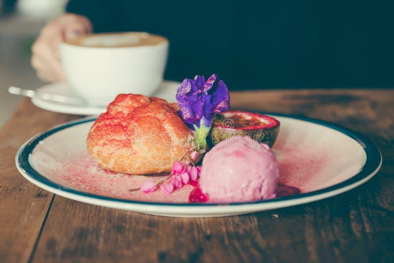 En maträtt av Choux lagar mat med grädde, rosa glass och passionfrukt med härlig garnering och kvinnan som dricker kaffe i bakgru arkivbild