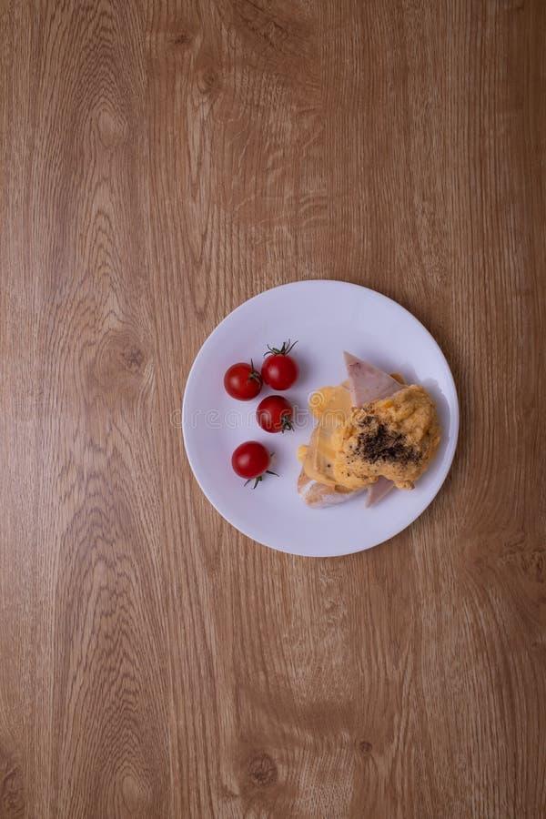 En maträtt av frukosten, äggröran, bröd, skinka och korven på den bruna wood texturtabellen arkivbilder