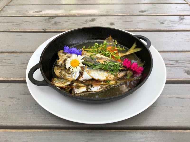 En maträtt av makrillen stekte i en svart panna för att laga mat och dekorerade med blommor grönsaker för rad för mat för bönamor royaltyfri fotografi