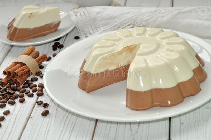 En maträtt med en aptitretande kaka för mousselager (vanilj och choklad) på en träyttersida dekorerade med kaffebönor arkivbilder