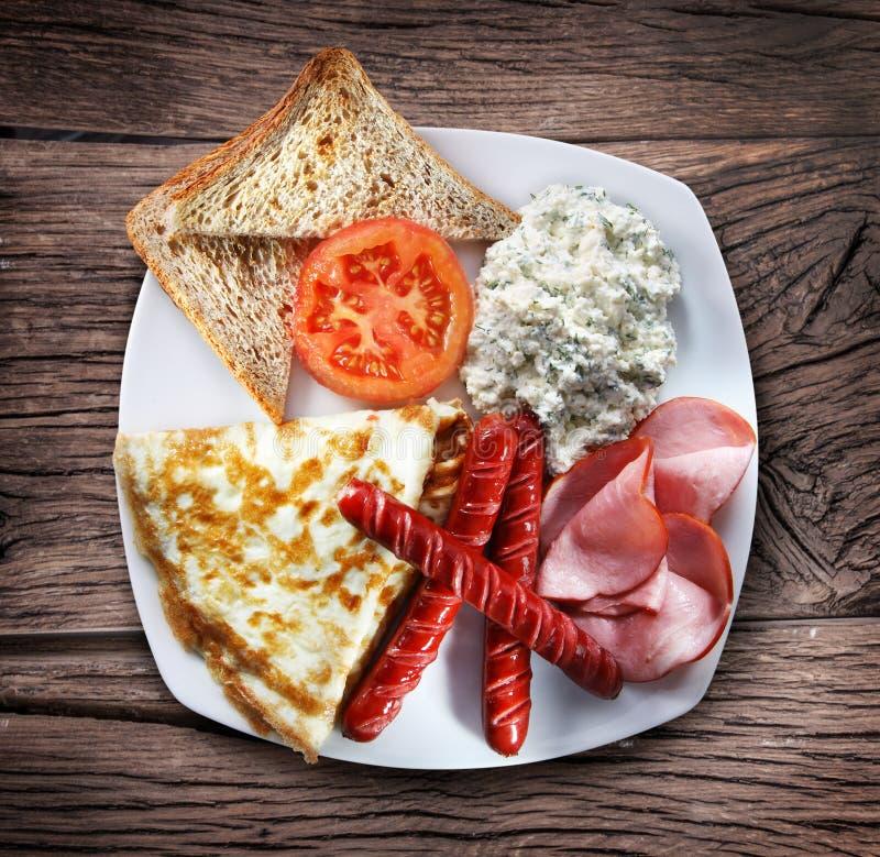 En maträtt med omelett, bacon och korvar arkivfoton