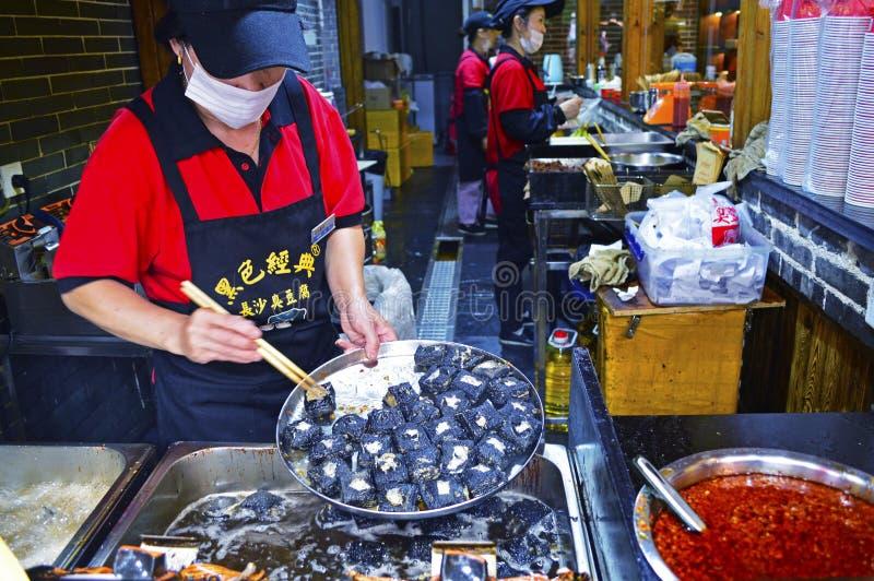 En matStallpersonal förbereder den Stinky tofuen på Changsha Kina arkivbild