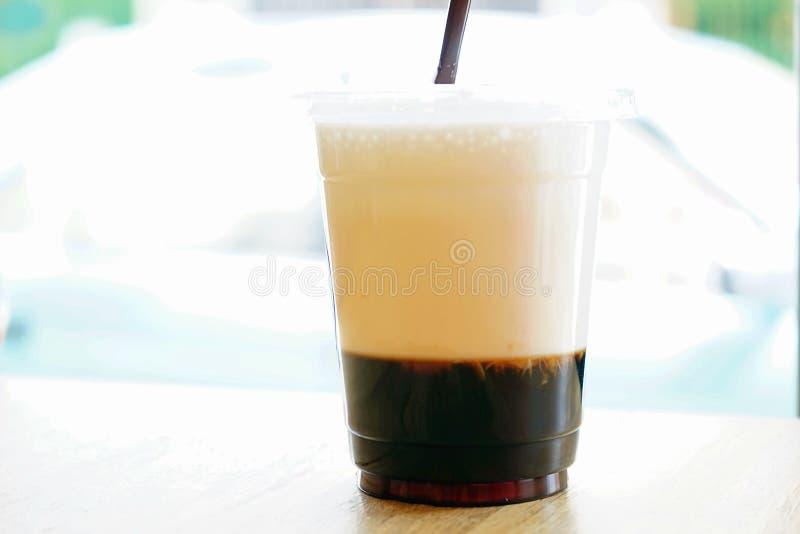 En med is dryck för två lager består av svart kaffe och mjölkar i plast- kopp med oskarp bokehbakgrund och kopierar utrymme fotografering för bildbyråer