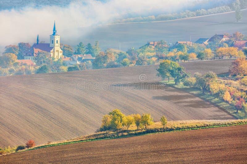 En by med en kyrka i den södra Moravian regionen härligt landskap under soluppgång med dimma, fält och det färgrika höstträdet fotografering för bildbyråer
