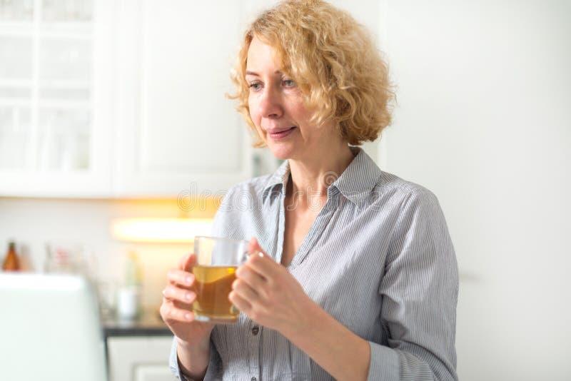 En medelålders kvinna rymmer en kopp te royaltyfri bild