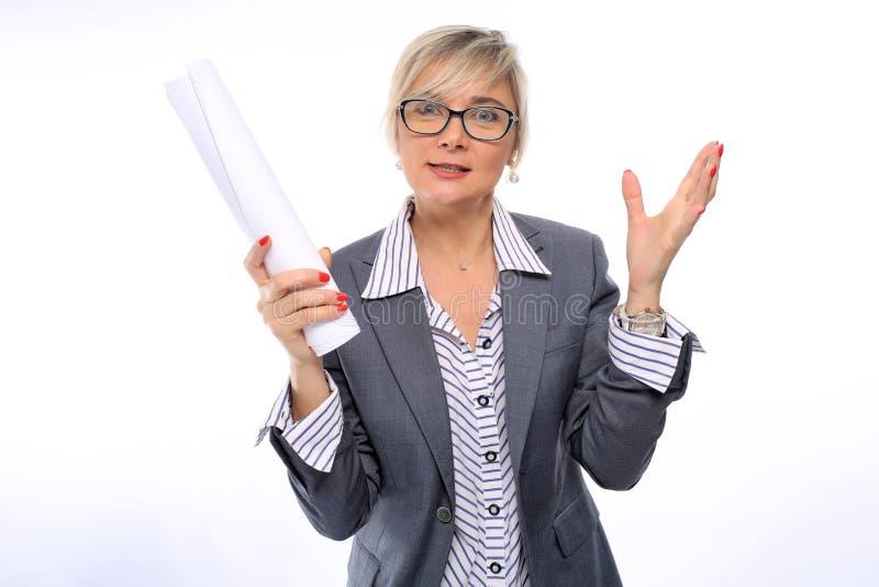 En medelålders lärare, 40 år som är gamla, i en vit randig skjorta, en grå dräkt och exponeringsglas, med en röd manikyr som rymm arkivfoton