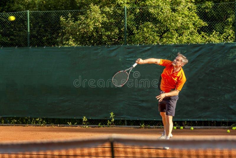 En medelålders man spelar tennis på en domstol med en naturlig jordyttersida på en solig sommardag arkivfoto