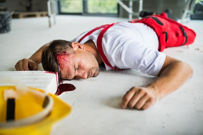 En medvetslös manarbetare som ligger på golvet efter olycka på konstruktionsplatsen royaltyfria foton