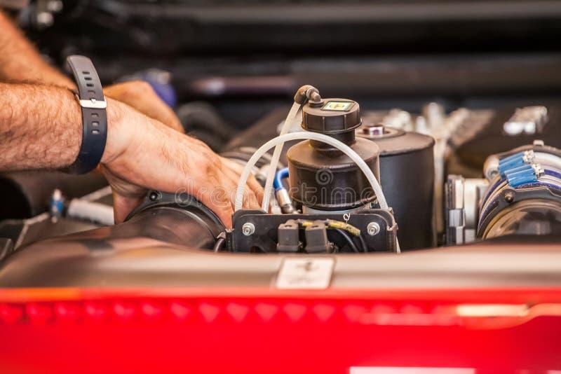 En mekaniker är granska och reparera motorn och några mekaniska delar av en supercar arkivfoto